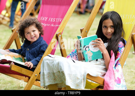 Hay Festival, Hay on Wye, Powys, Wales, UK - Friday 31st May 2019 - Two young readers enjoy the chance to sit and read in the deckchairs on the Festival lawns. The eleven day Festival features over 800 events many aimed at children. Photo Steven May / Alamy Live News - Stock Image