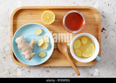 Lemon and ginger tea with honey. Wooden tray of honey lemon tea with fresh ginger root. - Stock Image