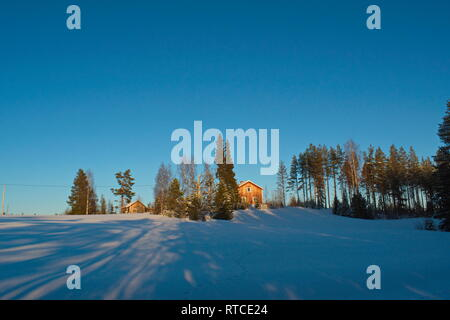 A farm house is illuminated by the low winter sun. The near forest is casting long shadows on the snow. - Stock Image