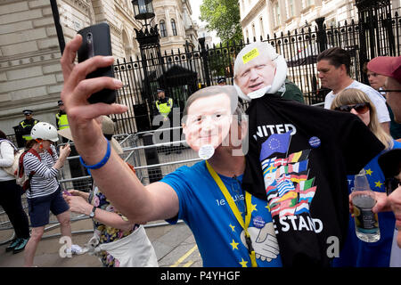 London, UK. 23rd June 2018. A protester wearing David Cameron and Boris Johnson masks takes a selfie outside 10 Downing Street. March for a Peoples Vote.  Credit: Scott Hortop/Alamy Live News. - Stock Image