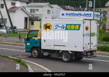 Small Yamato Transport truck featuring the company's 'kuro neko' (black cat) logo. Hokkaido, Japan. - Stock Image