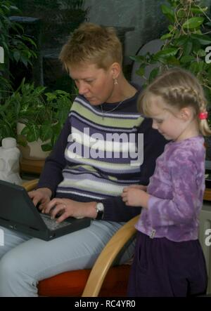 Mother engaged with laptop in the 2000s, no time to play with her daughter. - Stock Image