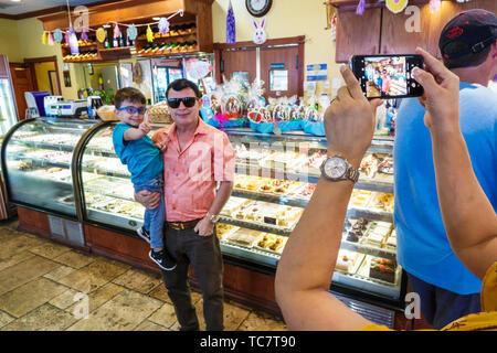 Miami Beach Florida North Beach Collins Avenue Buenos Aires Bakery & Cafe inside restaurant Hispanic food grandmother grandfather grandson boy smartph - Stock Image