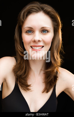 Head and shoulders portrait of young adult caucasian female smiling - Stock Image