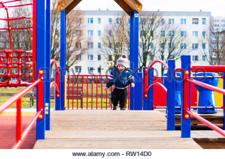 Poznan, Poland - February 24, 2019: Toddler boy in winter clothes walking on a wooden platform of a climb equipment on a playground in the Rataje park - Stock Image