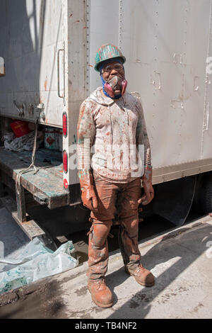 Posed portrait of a construction worker covered in paint on a subway renovation project on Roosevelt Ave. under the el in Queens, New York - Stock Image