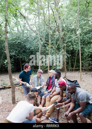 Mens group with maps and water bottles on hike in woods - Stock Image