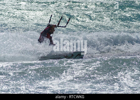 Kite boarder in the white foam during a windy day in french riviera - Stock Image