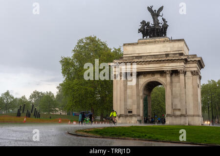 London, England, UK - May 2, 2019: Pedestrians and cyclists travel through Hyde Park Corner during a heavy rain storm in London. - Stock Image