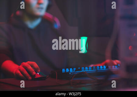 Close-up of busy man sitting at table with wires and using computer mouse while playing video game - Stock Image