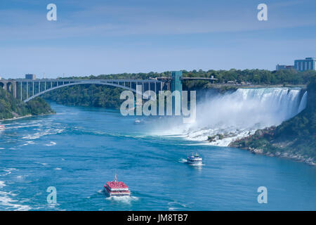 Looking toward the American Falls at Niagara Falls on a sunny day; Hornblower and Maid In The Mist are on the Niagara River. Sunny weather. - Stock Image