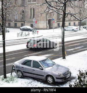 Strasbourg, Alsace, France, snowy street, parked car on pavement, traffic, - Stock Image