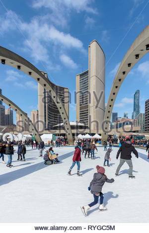 Toronto new city hall in winter with people skating on rink in Nathan Phillips Square in Toronto Ontario Canada - Stock Image