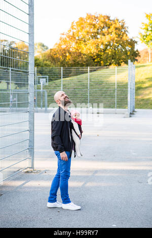 Father with baby girl in baby carrier on playing field - Stock Image