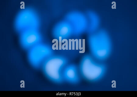 Abstract background with blue blurred spiral. Original harmonic texture with bright glowing round slices in caterpillar shape. Unusual bright backdrop. - Stock Image