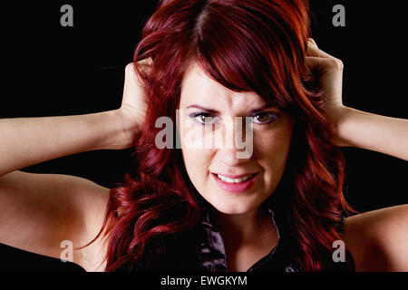 Stock image of frustrated female redhead over dark background - Stock Image