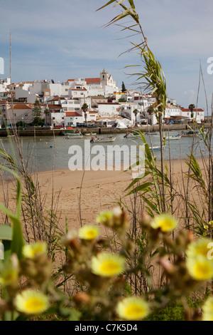 Portugal, Algarve, Ferragudo, View of Village & Bay through Flowers - Stock Image