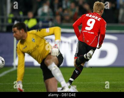 Mike Hanke of Hanover (R) scores the 4-3 against goalkeeper Tim Wiese of Bremen during the Bundesliga match Hanover - Stock Image