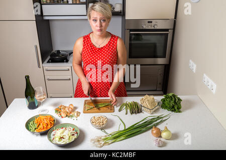 Surprised young woman in kitchen cutting asparagus - Stock Image