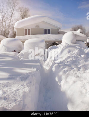 A house, roof and cars are covered with deep white snow in western new york for a weather or blizzard concept. - Stock Image