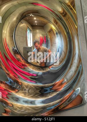Cleaning the toilet reflected in chrome flush  button. - Stock Image