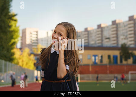 Cute european schoolgirl smiling at the camera, talking on smartphone. Apprentice secondary school intercommunicate by mobile device at schoolyard. Te - Stock Image