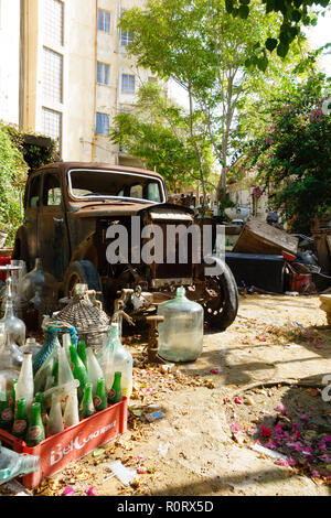 Back garden full of rubbish, antiques and an old rusty car. North Nicosia, Northern Cyprus October 2018 - Stock Image