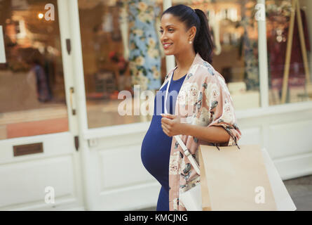 Smiling pregnant woman with shopping bags walking along storefront - Stock Image