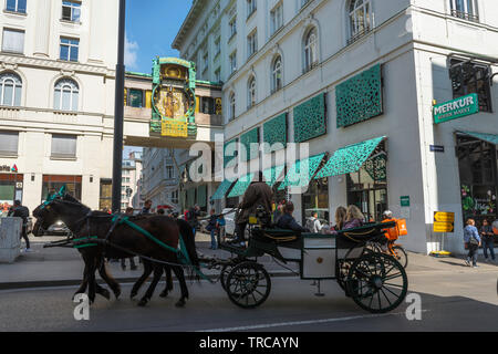 Vienna tourism, view of a horse drawn carriage containing tourists passing the Anker Clock in Hoher Markt in the Old Town area of Vienna, Austria. - Stock Image