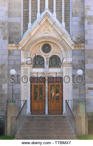 Montreal, Quebec, Canada-May 29, 2019: 'Chapel Notre-Dame de Lourdes'. Architectural details of an old door. The vintage building has stone walls. - Stock Image