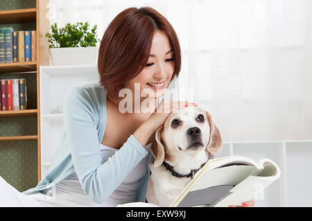 Young woman touching her dog and holding a book, - Stock Image
