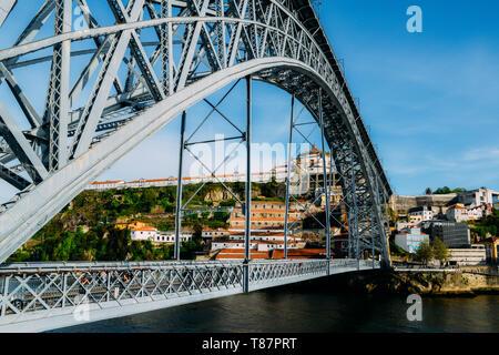 Porto, Portugal - April 29, 2019: Pedestrians on the Dom Luis I Bridge, a metal arch bridge that spans the Douro River - Stock Image