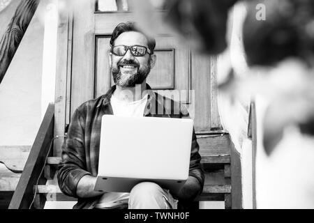 Black and white portrait of cheerful adult man working outdoor at home with personal notebook laptop computer - internet connection for free people co - Stock Image