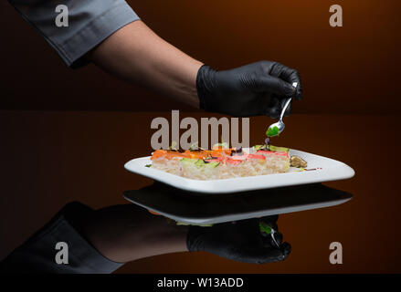chef decorates sushi with caviar. process of cooking sushi - Stock Image