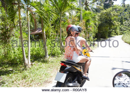 Young man and woman riding moped - Stock Image
