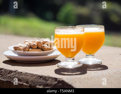 Poncha, a traditional alcoholic drink from the island of Madeira, Portugal, made with aguardente de cana and fresh passion fruit. Served along with pe - Stock Image