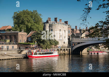 A river cruise boat berthed near Lendal Tower (formerly part of Yorks medieval wall defences) and Lendal bridge, - Stock Image