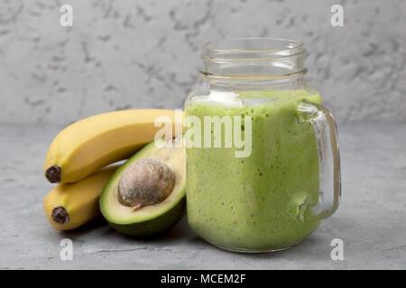 smoothies avocado banana in a mason jar, bananas and avocado on a gray concrete background - Stock Image