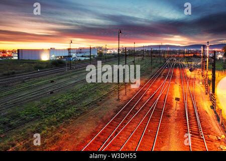 Sunset over a railroad with many tracks - Stock Image