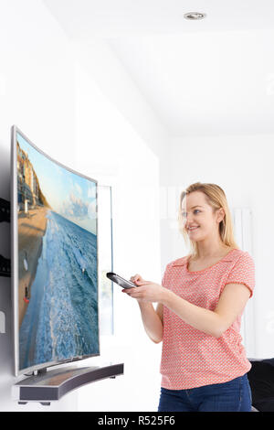 Young Woman With New Curved Screen Television At Home - Stock Image