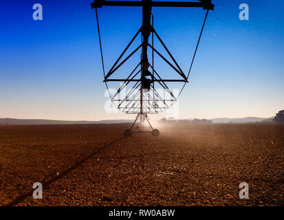 An overhead sprinkler water irrigation system  near Cordoba, Andalucia, Spain - Stock Image