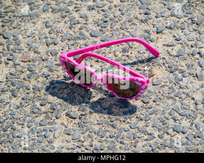 A pair of sunglasses lost on a seaside promenade with pink heart shaped frames - Stock Image