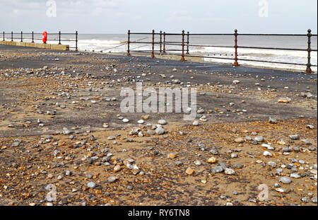 A view of the west promenade covered in stones thrown up by high seas on the North Norfolk coast at Cromer, Norfolk, England, United Kingdom, Europe. - Stock Image