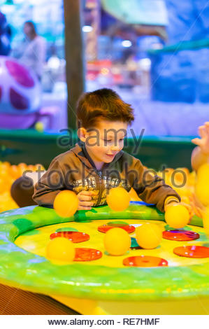 Kownaty, Poland - January 6, 2019: Young boy playing with plastic balls on a air blowing machine on a playground in the Majaland indoor amusement park - Stock Image