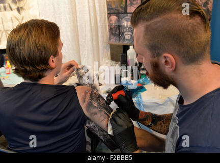 Garden City, New York, USA. September 13, 2015. R-L, GUNNAR VALDIMARSSON, from Akureyri, Iceland, is tattooing the - Stock Image