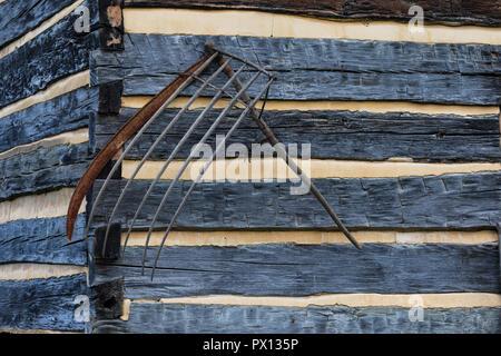 LIMESTONE, TN, USA:  A primitive hay rake hanging on a log cabin. - Stock Image
