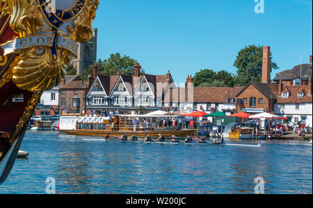 Henley on Thames, Berkshire, UK. 4th July, 2019. Henley Royal Regatta. 'Gloriana' the  90-foot-long British royal barge moored on the Thames river bank frames the rowers leaving the pontoon for the   Public Steamboat Alaska going past the backdrop of Henley town  Credit Gary Blake/Alamy Live - Stock Image