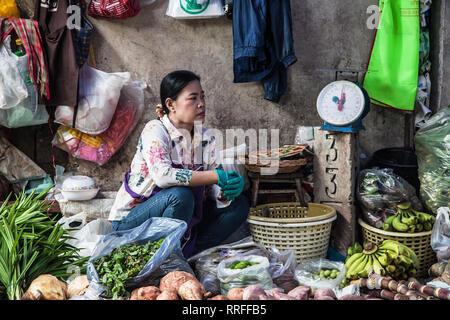Maeklong, Thailand - August 29, 2018: Woman at her stall in the Maeklong Railway Market, Samut Songkhram, Thailand. - Stock Image