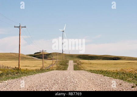 Wind turbine and transmission line in prairie landscape - Stock Image