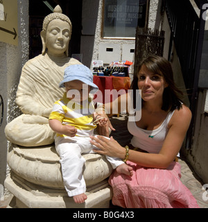 Mother and toddler sitting on Buddha statue outside a craft shop in Mijas Pueblo, Costa del Sol, Andalucia, Spain - Stock Image